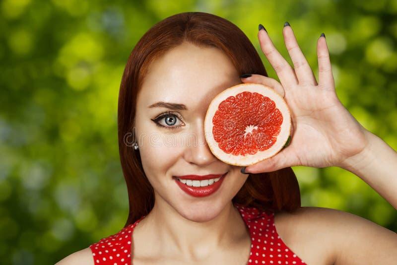 Portret van een roodharige jong meisje dat haar mond behandelt met de helft van een rode grapefruit stock fotografie