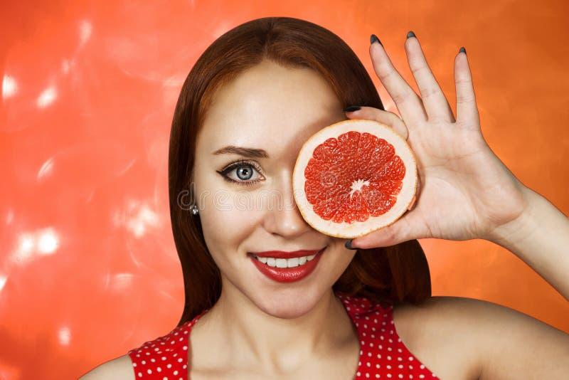 Portret van een roodharige jong meisje dat haar mond behandelt met de helft van een rode grapefruit stock afbeeldingen