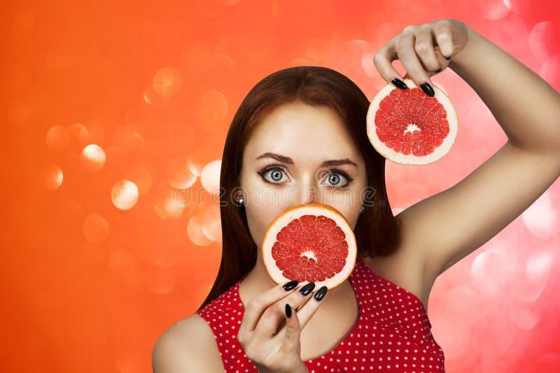 Portret van een roodharige jong meisje dat haar mond behandelt met de helft van een rode grapefruit stock foto