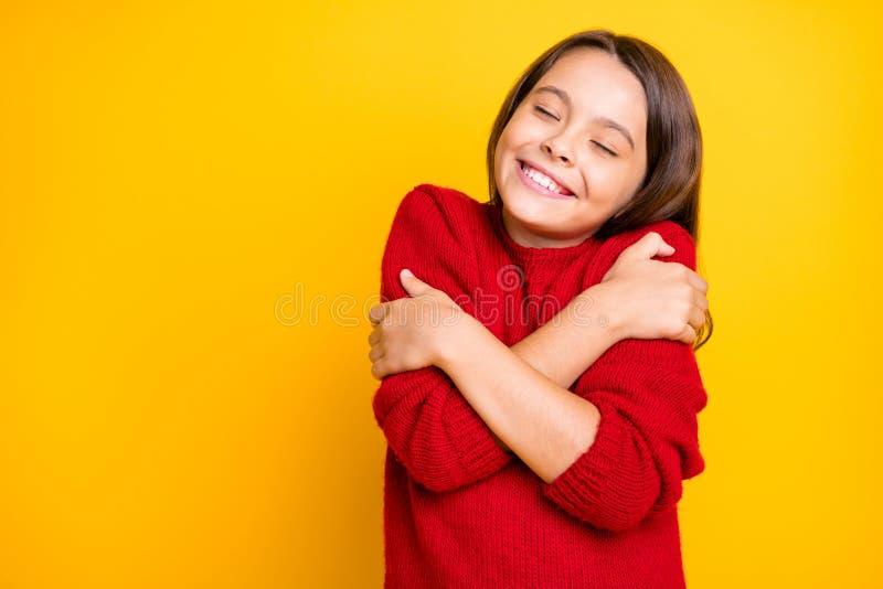 Portret van een rustig en kalm kind dat omhelst, geniet van een warme zachte comfy sweater pullover met rode, stijlvolle levensst royalty-vrije stock afbeeldingen