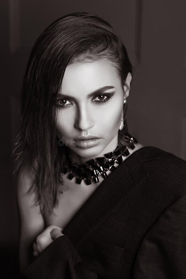 Portret van een schitterend meisje in de studio in een man jasje, een halsband met kort nat haar die de camera in BW bekijken royalty-vrije stock foto