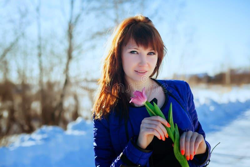 Portret van een schitterend mooi meisje in aard in de lente met een Tulp in haar handen royalty-vrije stock foto's
