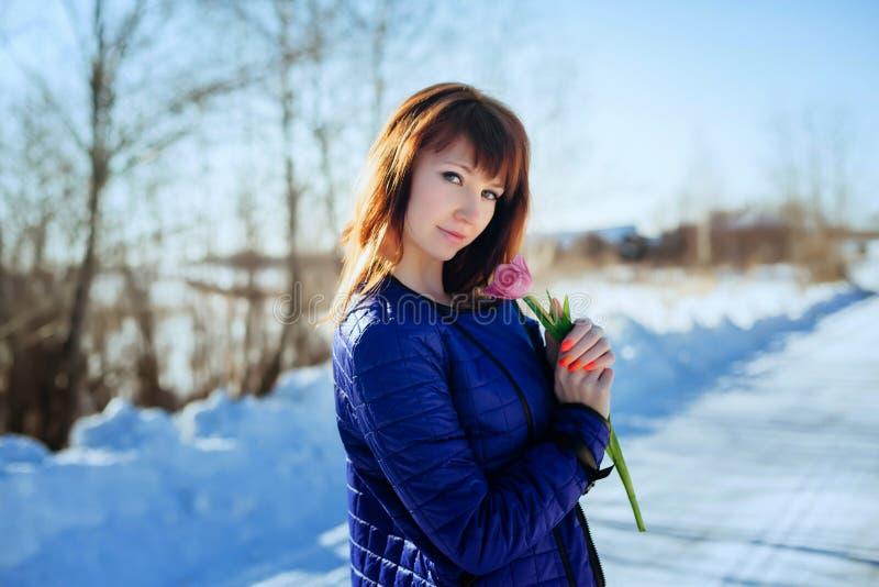 Portret van een schitterend mooi meisje in aard in de lente met een Tulp in haar handen royalty-vrije stock foto