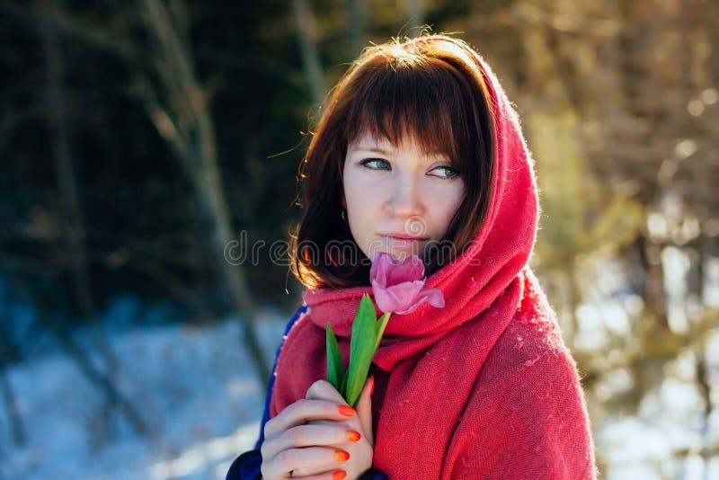 Portret van een schitterend mooi meisje in aard in de lente met een Tulp in haar handen stock foto