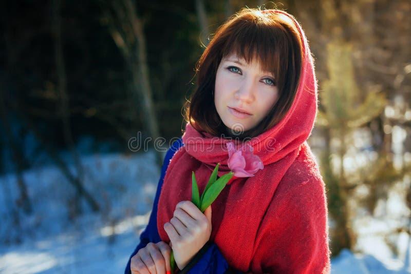 Portret van een schitterend mooi meisje in aard in de lente met een Tulp in haar handen stock afbeelding