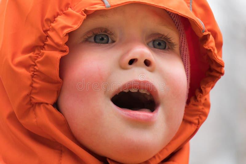 Portret van een schreeuwend kind in een kap en warme kleren royalty-vrije stock afbeelding