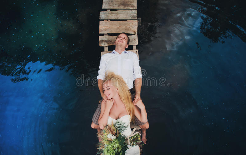 Portret van een sensueel jong paar die op een houten brug koesteren royalty-vrije stock fotografie