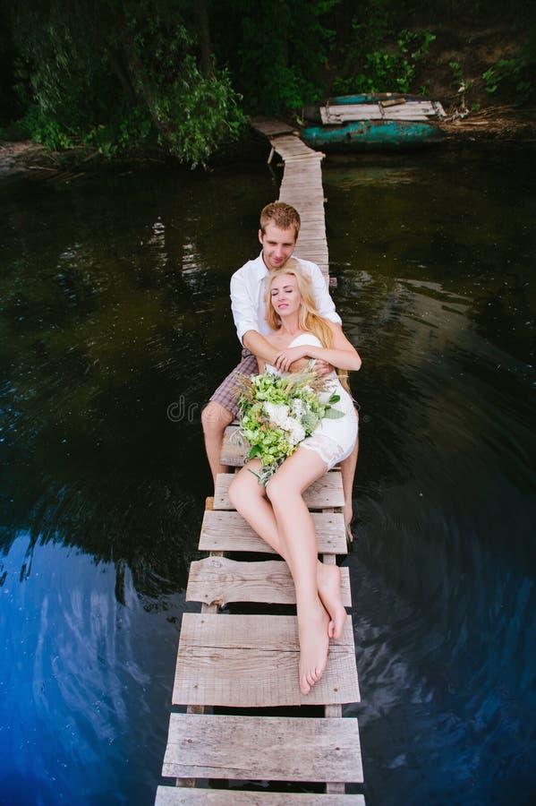 Portret van een sensueel jong paar die op een houten brug koesteren stock foto