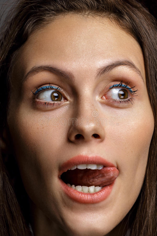 Portret van een sensuele mooie jonge vrouw die lange tong tonen stock foto's