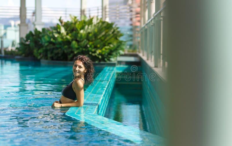 Portret van een sexy glimlachende Kaukasische vrouw in zwempak het ontspannen in een dakpool met groene struiken en stadsmeningen royalty-vrije stock afbeeldingen