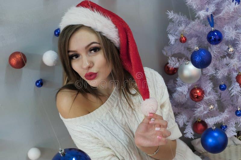Portret van een sexy langharig blonde in een Santa Claus-hoed en gebreide sweater met een naakte schouder Lippen in de vorm van e royalty-vrije stock afbeeldingen