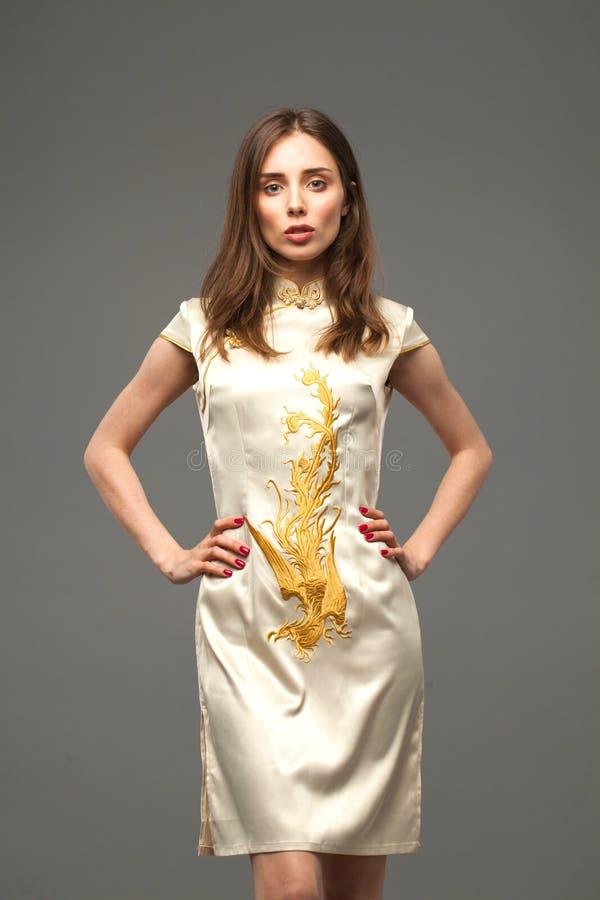 Portret van een slank mooi meisje in een Aziatische elegante kleding met een draakdruk royalty-vrije stock afbeeldingen