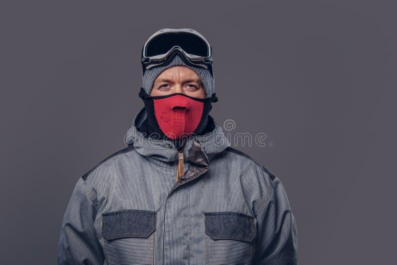 Portret van een snowboarder gekleed in een volledig beschermend toestel voor extream het snowboarding stellen bij een studio Geïs royalty-vrije stock afbeeldingen