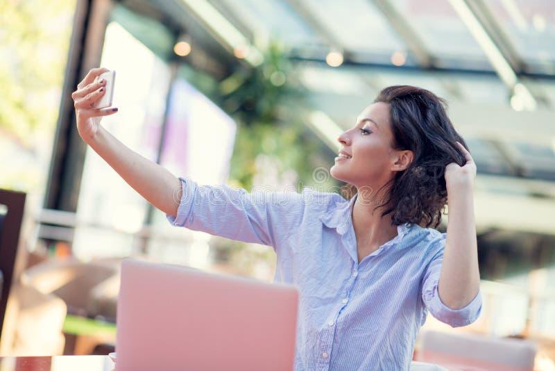 Portret van een speels jong meisje die selfie met mobiele telefoon nemen terwijl in openlucht het zitten met laptop computer bij  royalty-vrije stock afbeeldingen