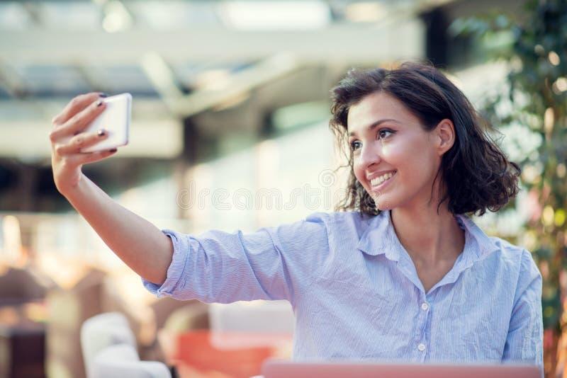 Portret van een speels jong meisje die selfie met mobiele telefoon nemen terwijl in openlucht het zitten met laptop computer bij  royalty-vrije stock afbeelding