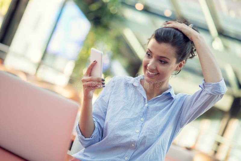 Portret van een speels jong meisje die selfie met mobiele telefoon nemen terwijl in openlucht het zitten met laptop computer bij  royalty-vrije stock foto's