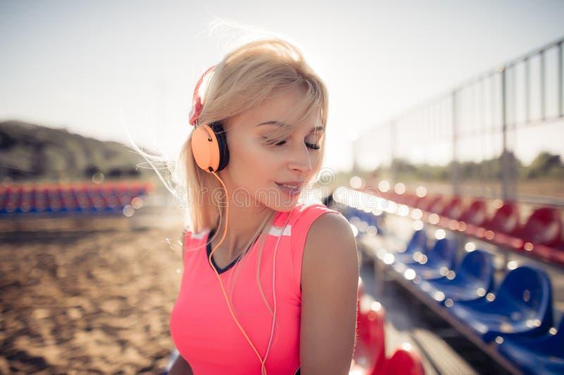 Portret van een sportief adolescentiemeisje die van het uitoefenen, luisterend aan muziek met hoofdtelefoons rusten, die in openl royalty-vrije stock afbeeldingen