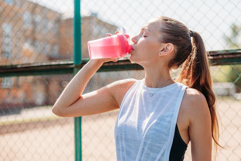 Portret van een sportieve jonge sexy vrouw die koel water van een fles op een de zomersportterrein drinken royalty-vrije stock afbeelding
