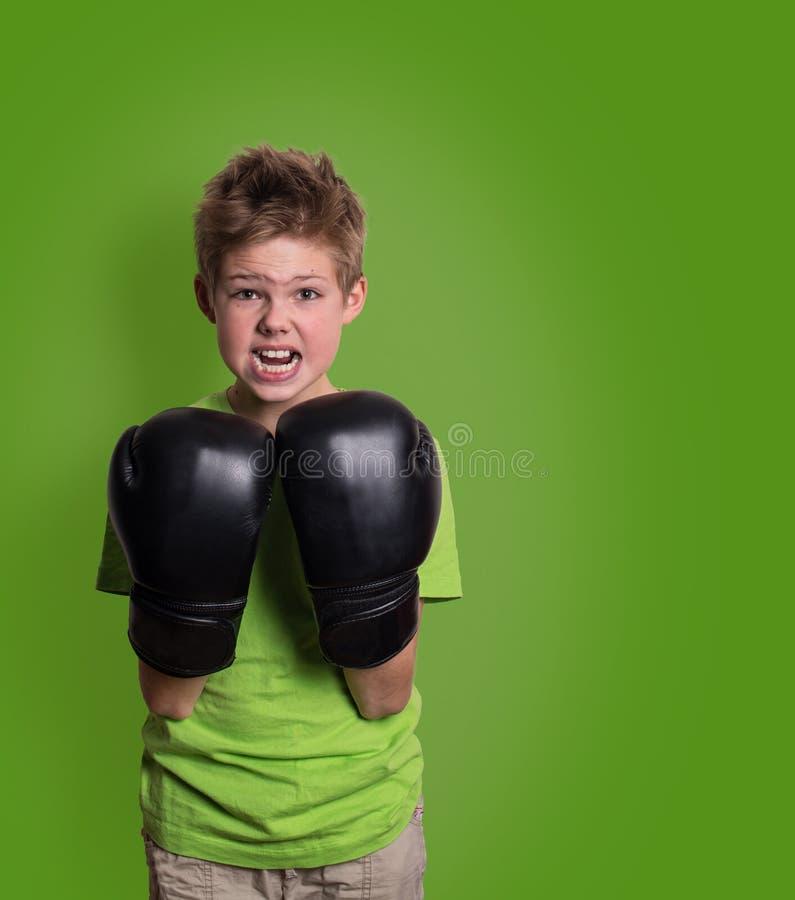 Portret van een sportieve jongen belast met het in dozen doen met copyspace boos stock foto's