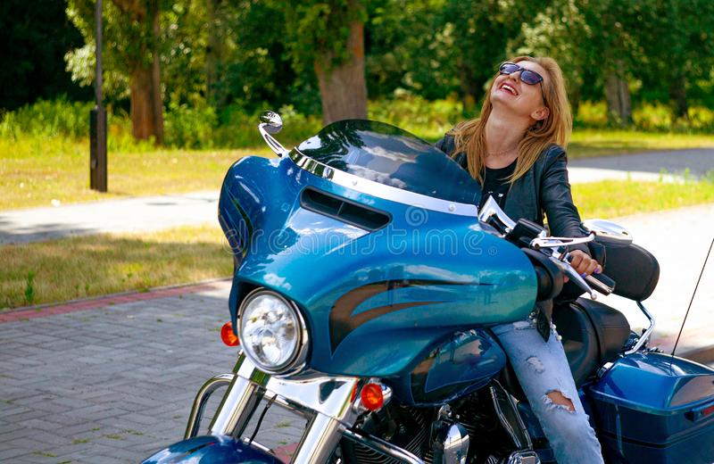 Portret van een sterke en onafhankelijke zitting van de blondevrouw op motorfiets in de stad royalty-vrije stock foto