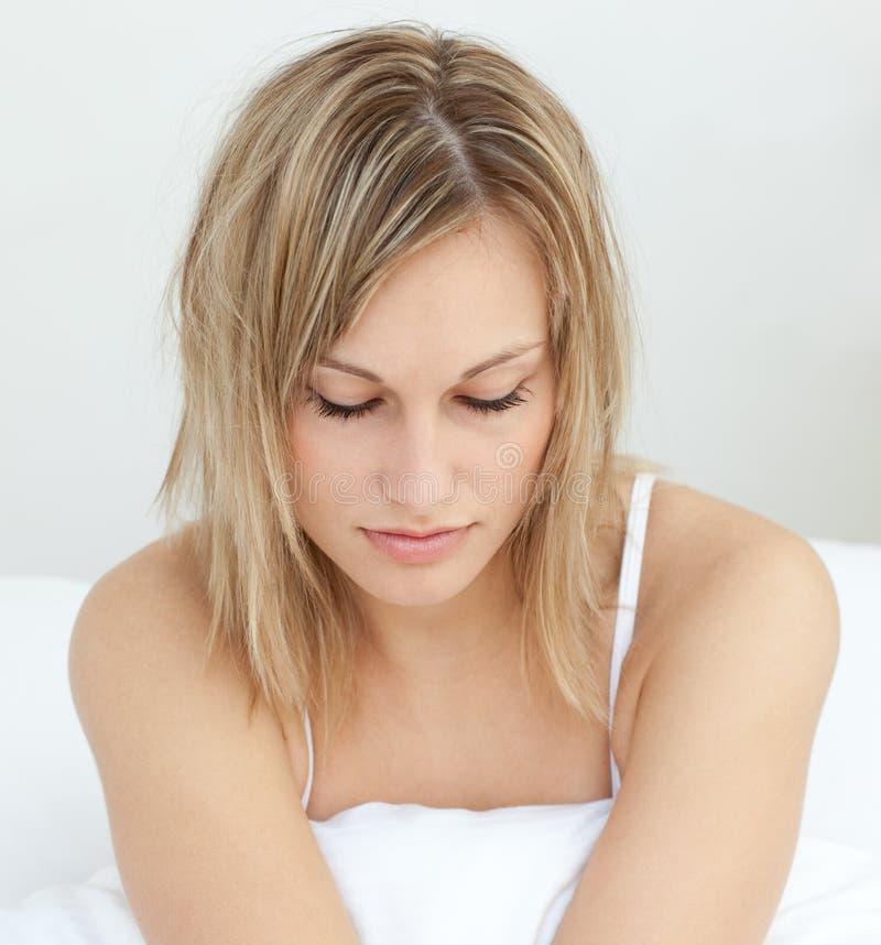 Portret van een stralende vrouwenzitting op haar bed stock fotografie