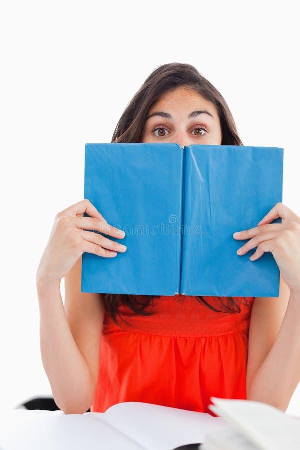 Portret Van Een Student Die Achter Een Blauw Boek Verbergt Royalty-vrije Stock Afbeelding
