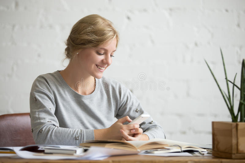 Portret van een studentenmeisje bij het bureau met telefoon stock afbeelding