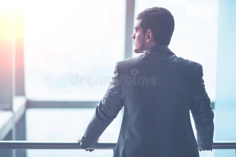 Portret van een succesvolle knappe zakenman voor een venster, is er een lege ruimte voor tekst stock afbeelding