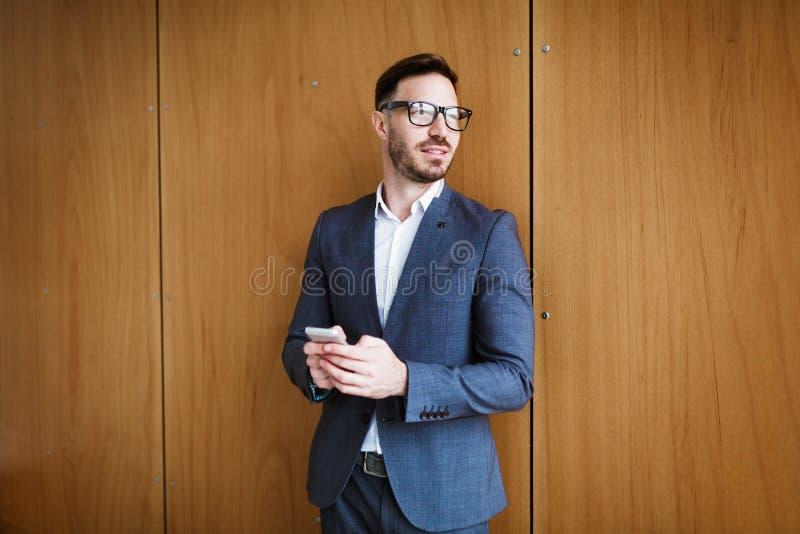 Portret van een succesvolle zakenman die glazen en kostuum dragen stock foto
