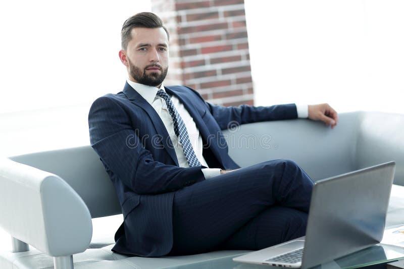 Portret van een succesvolle zakenmanzitting in de bureauhal royalty-vrije stock foto's