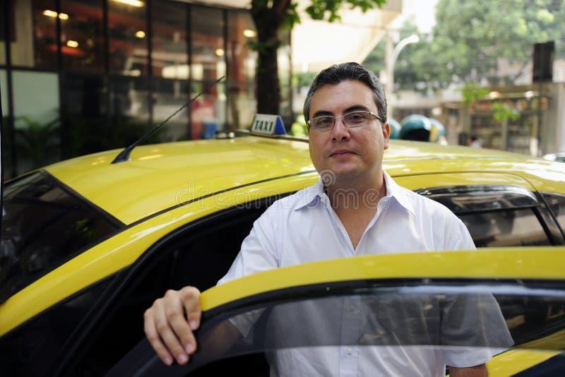 Portret van een taxibestuurder met cabine stock afbeelding