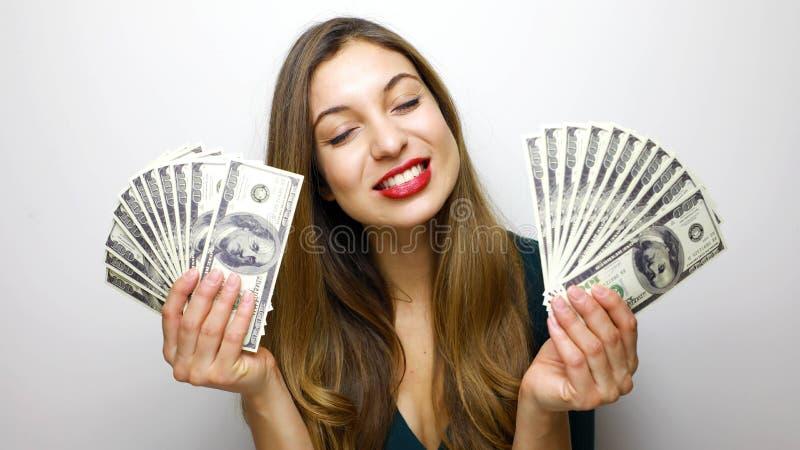 Portret van een tevreden jonge die bos van de vrouwenholding van geldbankbiljetten over witte achtergrond worden geïsoleerd stock fotografie