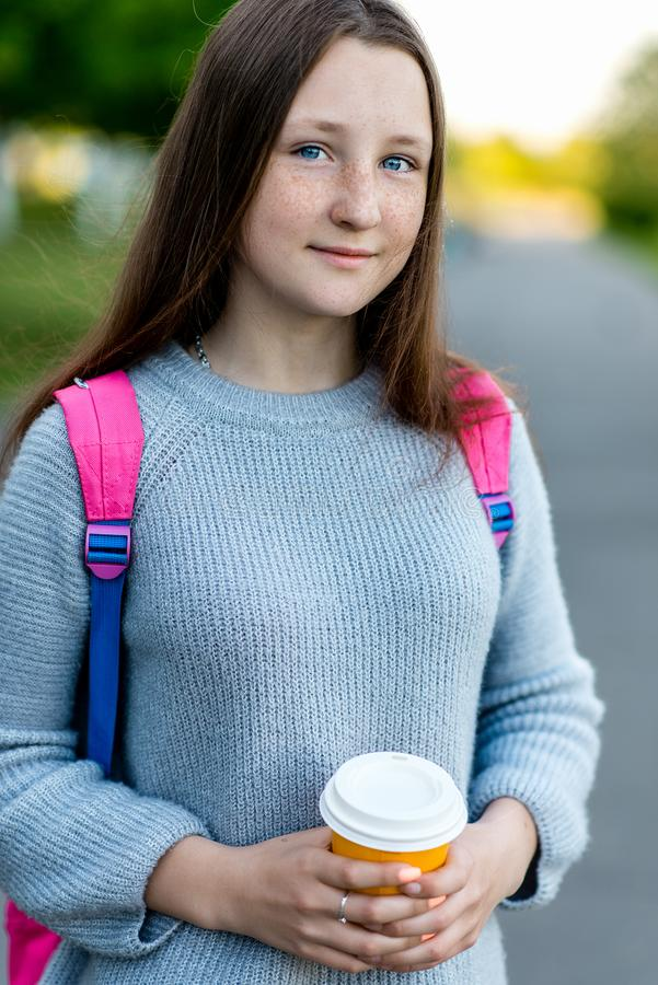 Portret van een tienerclose-up De zomer in aard In de handen van een hete kop van koffie of thee Achter de rugzak stock afbeelding