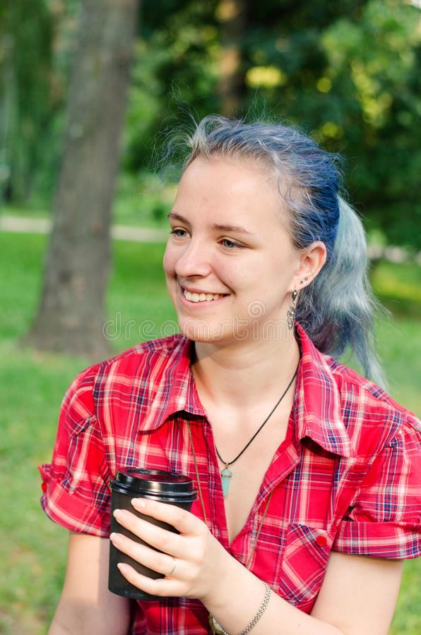 Portret van een toevallig leuk en jong meisje met blauw haar in jeans in stedelijke de zomer het drinken koffie stock fotografie