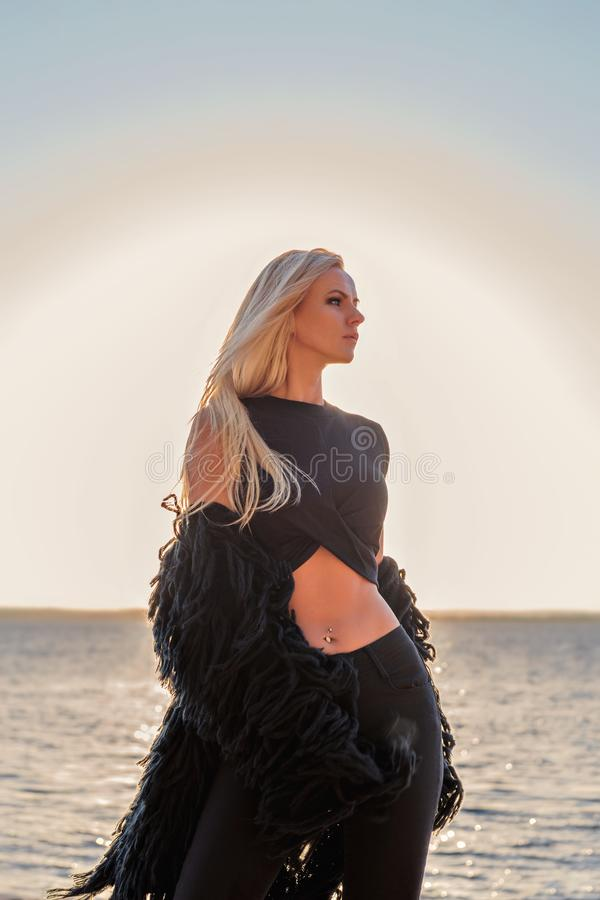 Portret van een verleidelijk sexy blonde die zich pensively in zwarte kleren met een zonsondergangmeer bevinden op een achtergron royalty-vrije stock foto's