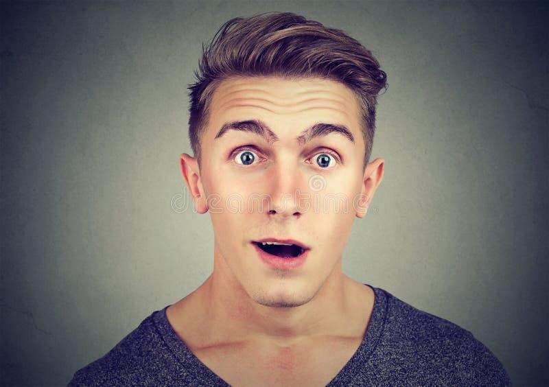 Portret van een verraste jonge mens die camera bekijken royalty-vrije stock afbeeldingen