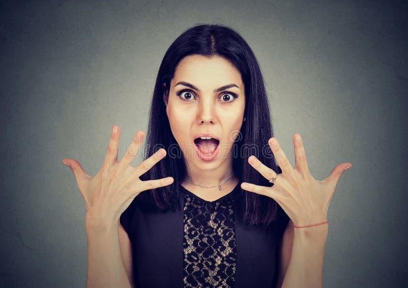 Portret van een verraste jonge vrouw met brede open mond en handen omhoog in lucht royalty-vrije stock afbeeldingen