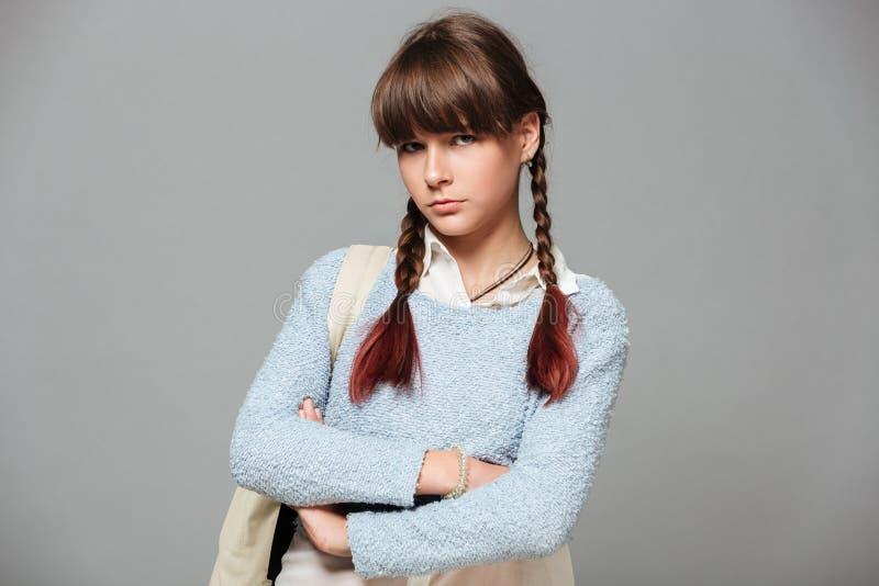 Portret van een verstoord droevig schoolmeisje die zich met gevouwen wapens bevinden royalty-vrije stock foto's