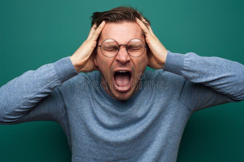 Portret van een verstoorde jonge mens die zijn hoofd clutching stock foto