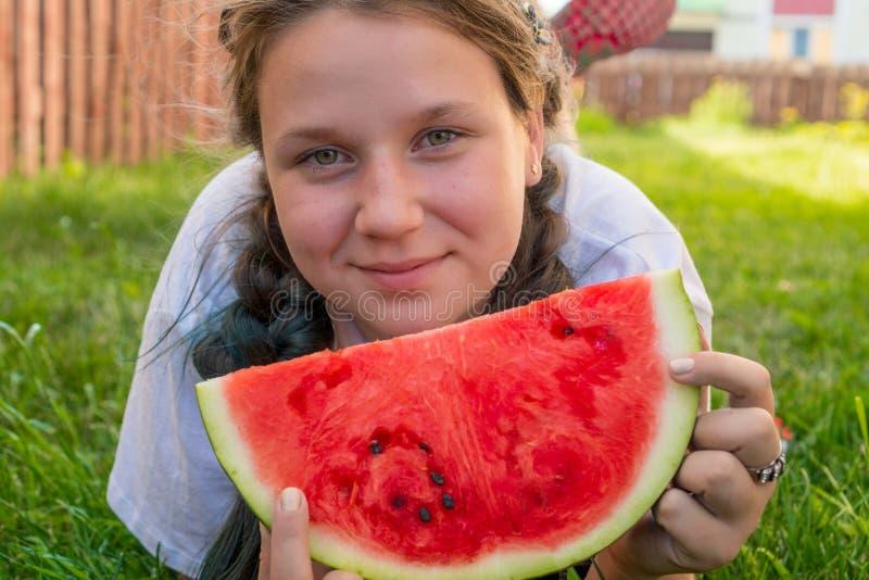 Portret van een vet meisje van 13 jaar oud wie op het gras met een watermeloen in haar handen ligt royalty-vrije stock fotografie