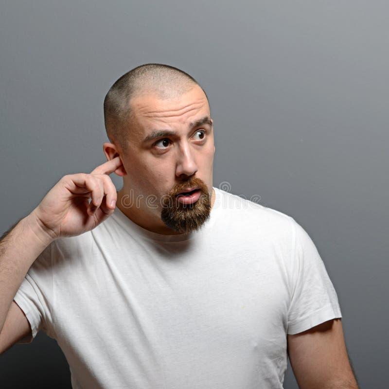 Portret van een vinger van de mensenholding in oor tegen grijze achtergrond stock afbeeldingen