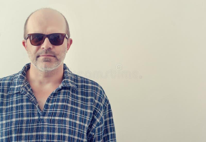 Portret van een volwassen mens met een grijze baard met donker gestemd glazenoverhemd op een lichte achtergrond, stock afbeeldingen