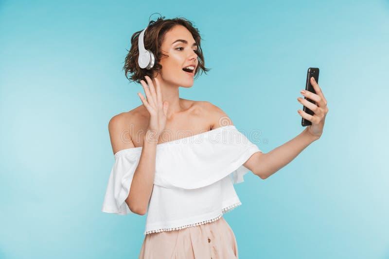 Portret van een vriendschappelijke jonge vrouw die aan muziek luisteren royalty-vrije stock foto's