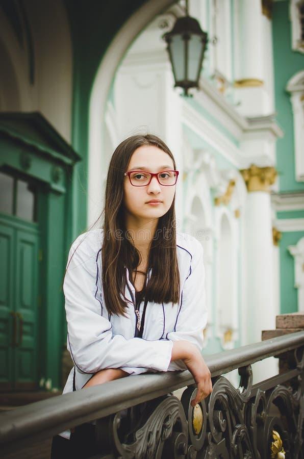 Portret van een vrij jong meisje met glazen op de achtergrond van een mooi oud gebouw royalty-vrije stock fotografie
