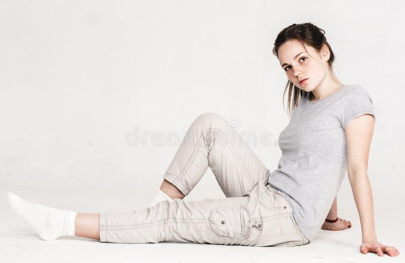 Portret van een vrij jonge die zitting van het vrouwenmeisje op de vloer op wit wordt geïsoleerd stock foto's