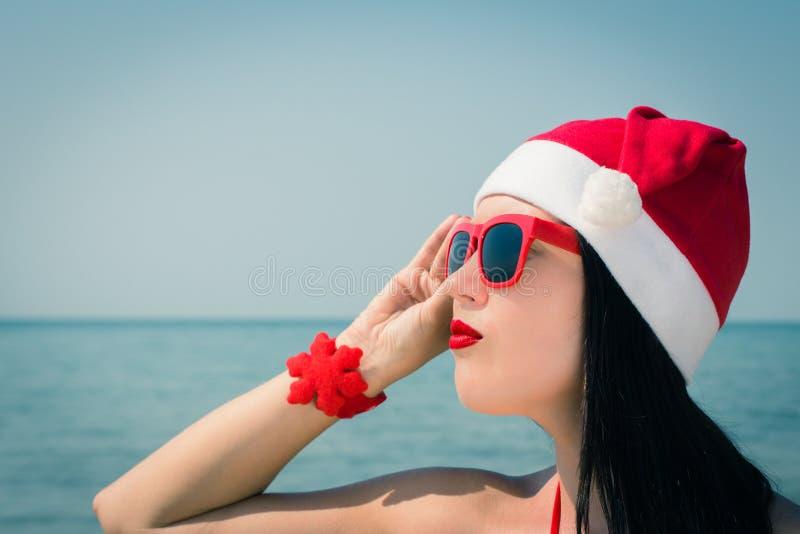 Portret van een vrij jonge vrouw in Santa Claus-hoed en sunglass stock foto