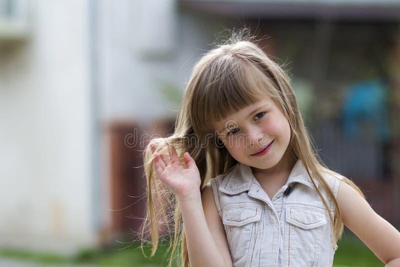 Portret van een vrij weinig langharig blond kindmeisje in slee stock afbeelding