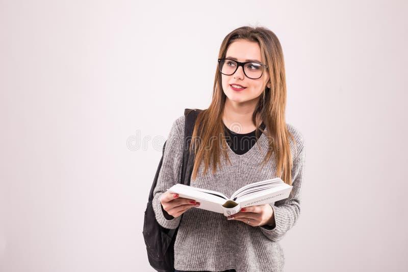 Portret van een vrolijk glimlachend Afrikaans studentenmeisje die rugzak dragen die en boeken houden over wit worden geïsoleerd royalty-vrije stock afbeeldingen