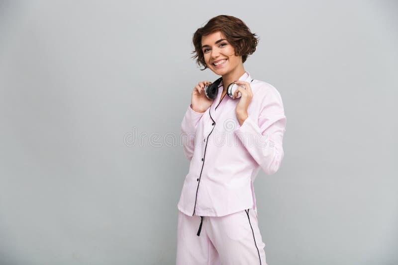 Portret van een vrolijk glimlachend meisje in pyjama's met hoofdtelefoons royalty-vrije stock afbeeldingen