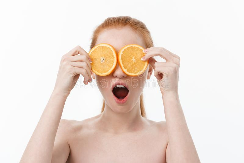 Portret van een vrolijk jong meisje die twee plakken van een sinaasappel houden bij haar gezicht over witte muurachtergrond stock afbeelding